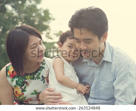 asian family playing and enjoying quality time outdoor , vintage tone - stock photo