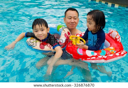 asian family playing on swimming pool