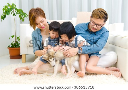 Asian family playing with pet in the living room - stock photo