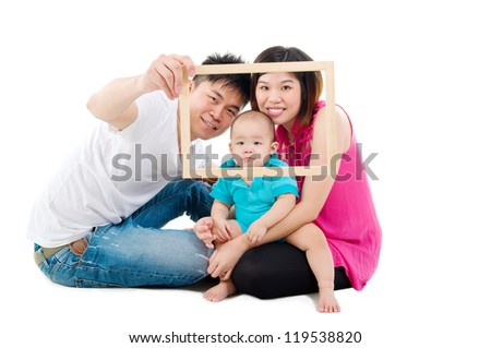 Asian family posing with a wood frame - stock photo