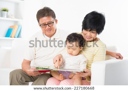 Asian family reading book sitting on sofa indoor, grandparents and grandchild living lifestyle at home. - stock photo