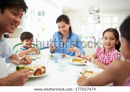 Asian Family Sitting At Table Eating Meal Together - stock photo