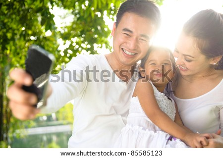 Asian Family Taking Photographs in the park - stock photo