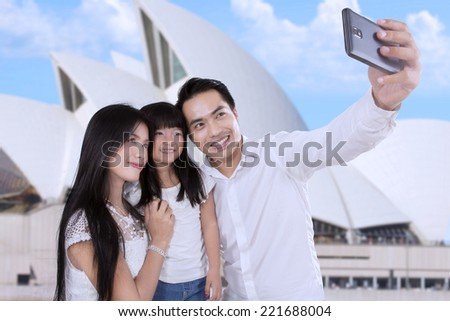 Asian family taking self portrait together at Opera House in Sydeny - stock photo