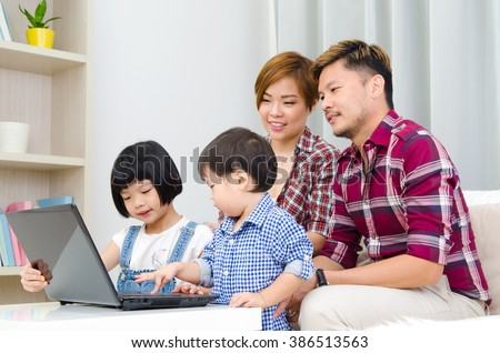 Asian family using laptop at home