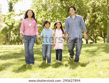 Asian family walking hand in hand in park