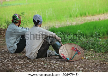 Asian farmers taking a rest on the side of a paddy field after working time. Agriculture is one of the most important industries of the region.