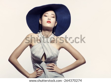 Asian fashion model in hat against white background - stock photo