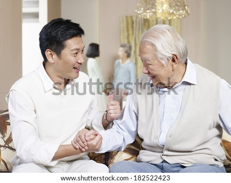 asian father and adult son chatting on couch