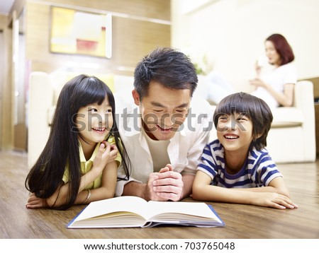 asian father and children lying on floor reading book with mother in the background.