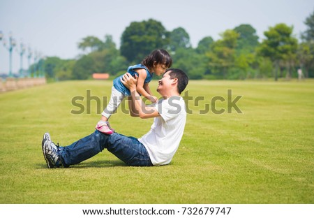 Asian father and daughter are playing together in the park with happiness moment on the sunny day, concept of love and relation in family life.