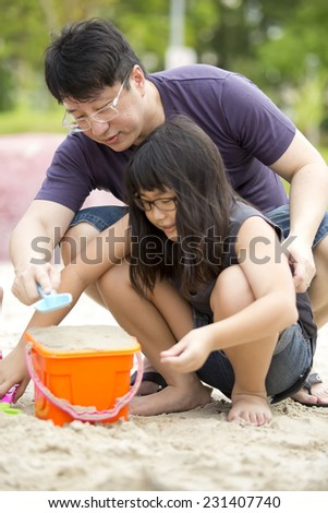 Asian father and daughter playing sand in park