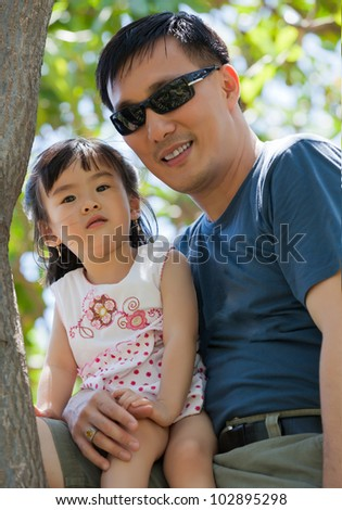 Asian Father and Daughter sitting in a tree - stock photo