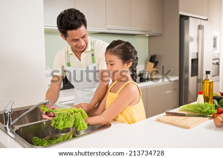 Asian father and daughter washing fresh lettuce for the salad - stock photo