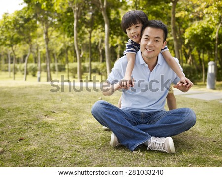 asian father and elementary-age son enjoying outdoor activity in park. - stock photo