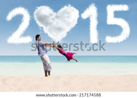 Asian father and his daughter playing at beach under cloud of 2015 - stock photo
