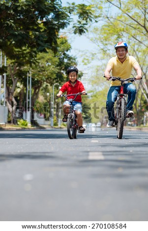 Asian father and son enjoying cycling together - stock photo