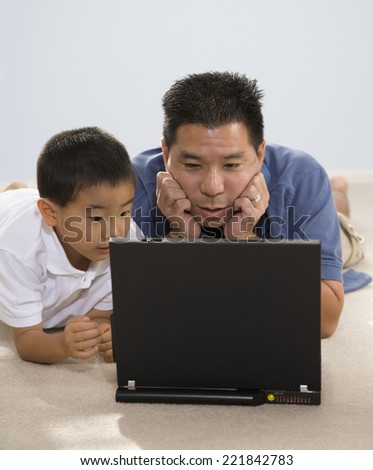 Asian father and son looking at laptop