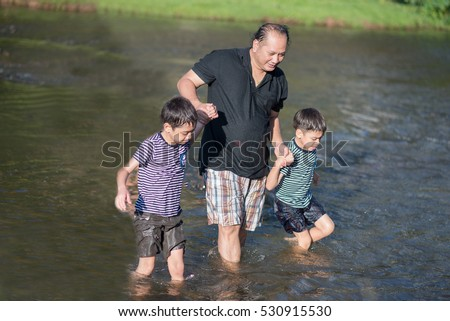 Asian father carry sons on back cross over the river with happy face