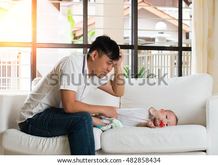 asian father having trouble chaging diaper