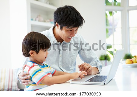 Asian Father Helping Son To Use Laptop At Home - stock photo