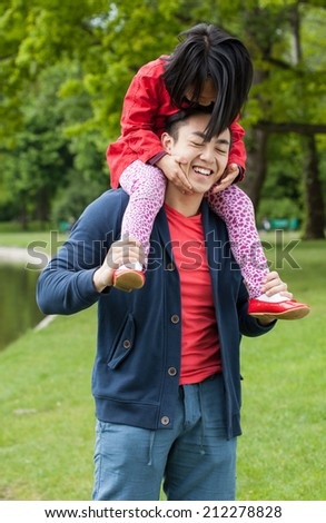 Asian father with daughter in park, vertical - stock photo
