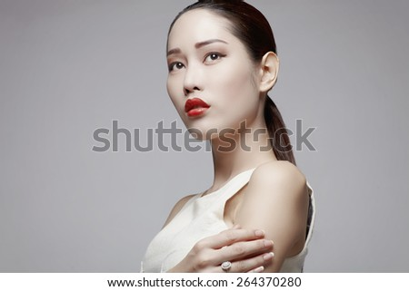 Asian female beauty model in studio against gray background - stock photo