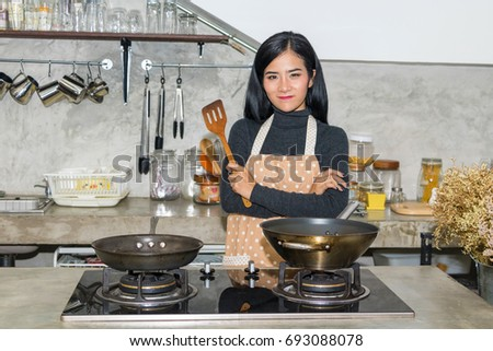 Asian female chef is cooking in the kitchen.