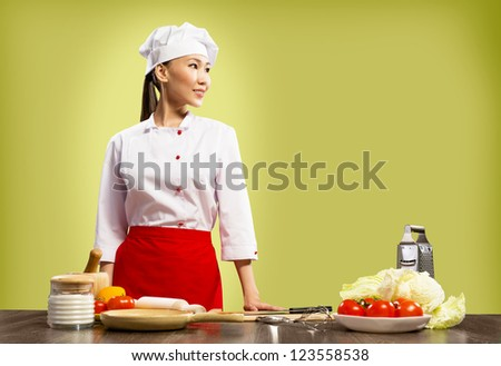 Asian female chef looking at the space for text