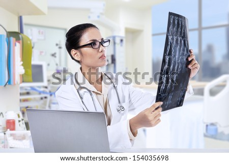 Asian female doctor holding x-ray results and using her laptop computer at clinic - stock photo
