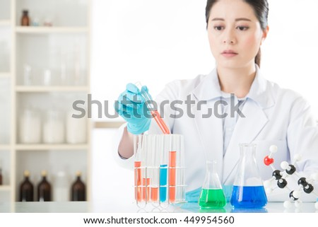Asian female forensic scientist working on chemicals in laboratory - stock photo