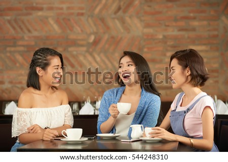 Asian female friends laughing when chatting in cafe