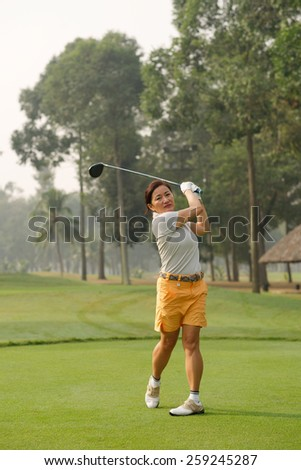 Asian female golf player teeing off