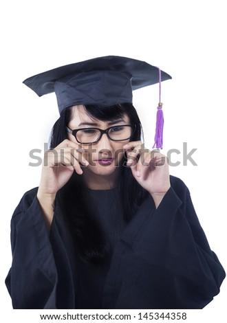 Asian female graduate is crying on white background - stock photo