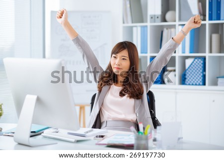 Asian female manager stretching while sitting at the computer - stock photo