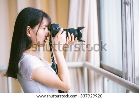 asian female shoting with camera  - stock photo