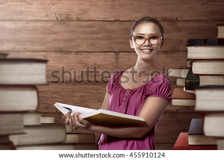Asian female student carry a lot of books ready for study - stock photo