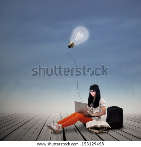 Asian female student is working on laptop under lit bulb outdoor - stock photo