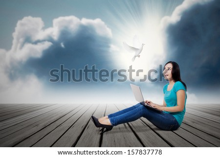 Asian female student looking at dove with laptop outdoor