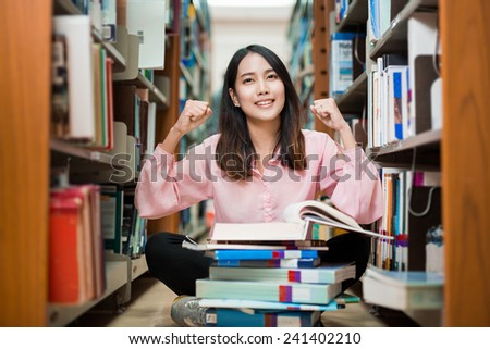 Asian female student was delighted to find the answer in the book. The University Library - stock photo