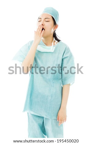 Asian female surgeon yawning with hand over mouth - stock photo