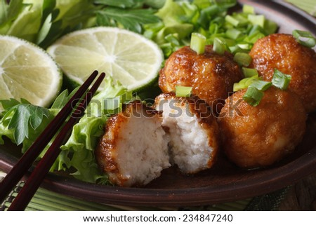 Asian fish balls with lime and salad on a plate macro. horizontal  - stock photo
