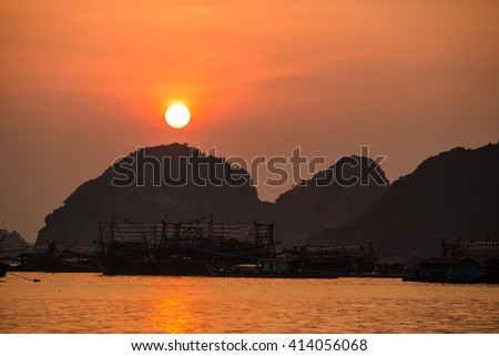 Asian fishing boats at sunset on a background of mountains. - stock photo