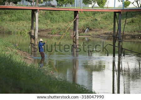 asian fishman at river with nets