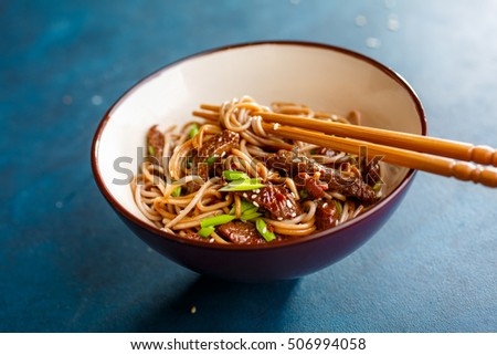 Asian food. Asian soba noodles with beef and sesame in a bowl.