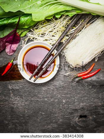 Asian food background with soy sauce, chopsticks, rice noodles and vegetables for tasty Chinese or Thai cooking, top view - stock photo