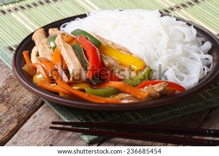 Asian food: chicken with vegetables and rice noodles close up with chopsticks on the table. horizontal  - stock photo