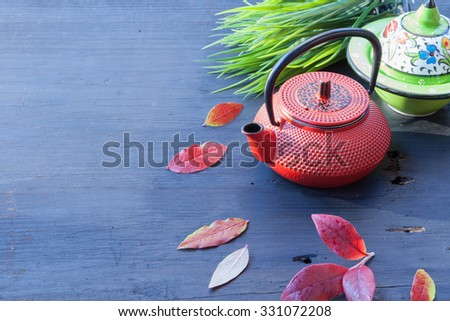 Asian food concept, tea pot, herbs and leaves on old wooden table against a rising sun - stock photo