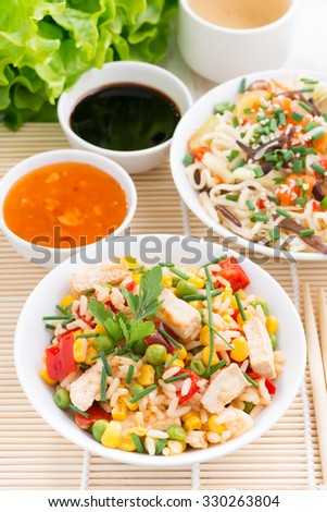 Asian food - fried rice with tofu, noodles with vegetables and herbs, top view, vertical - stock photo