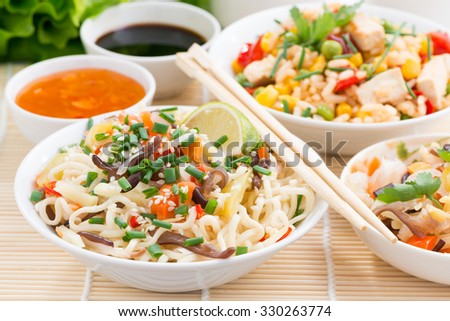 Asian food - noodles with vegetables and greens, fried rice with tofu, close-up, horizontal - stock photo